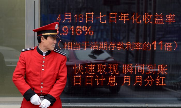 A guide stands in front of a bank in Beijing, April 23. (Wang Zhao/AFP/Getty Images)