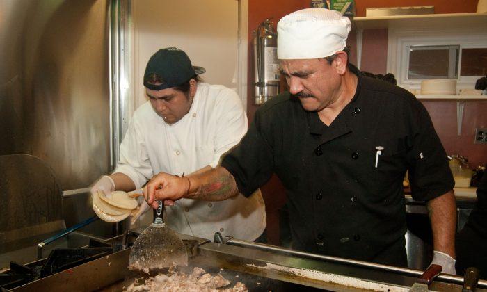 Galdino Molinero (R), also widely known as Tortas, making carnitas tacos. (Joshua Philipp/Epoch Times)