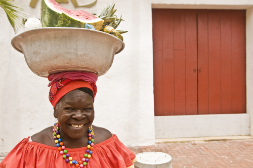 A woman carries fruit in Cartagena, Colombia. More Americans have been retiring to Latin America and more are expected, reports Cuenca High Life. (Shutterstock*)