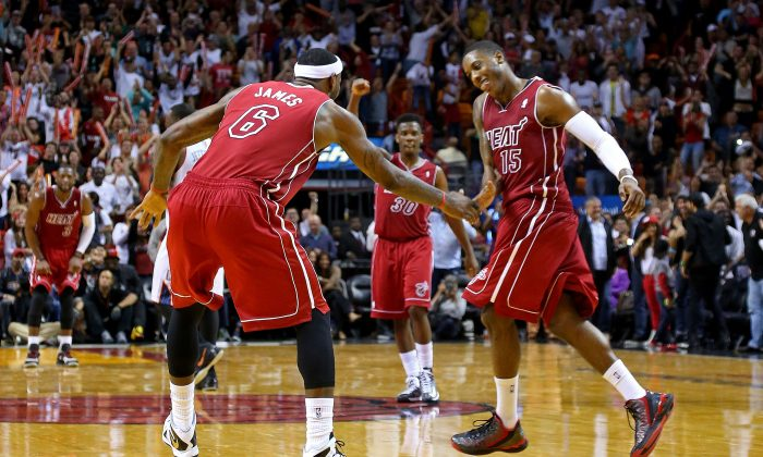 LeBron James #6 and Mario Chalmers #15 of the Miami Heat high five during a game against the Charlotte Bobcats at American Airlines Arena on December 1, 2013 in Miami, Florida. (Mike Ehrmann/Getty Images)