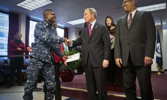 Philip Essienyi, navy petty officer 3rd class from Ghana (L), shakes hands with Mayor Michael Bloomberg after receiving his certificate of citizenship during a naturalization ceremony in New York, Dec. 18, 2013 (Bebeto Matthews/AP)