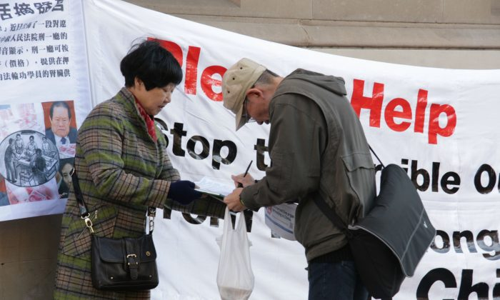A passerby in Sydney, Australia, signs a petition calling for an end to the atrocity of forced organ harvesting of Falun Gong practitioners in China, on July 6, 2013. The signature is one of nearly 1.5 million from across the world presented to the office of the U.N. High Commissioner for Human Rights on Dec. 9, 2013. (Minghui.org)