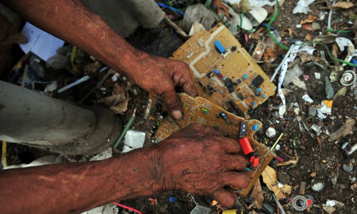 A man collects copper from an electronic circuit to sell for recycling, in a landfill of Managua, Nicaragua, on Jan. 11, 2013. E-waste is among the top environmental issues facing our world in 2014; new products are entering the market aimed at giving us our high-tech devices with less waste. (Hector Retamal/AFP/Getty Images)