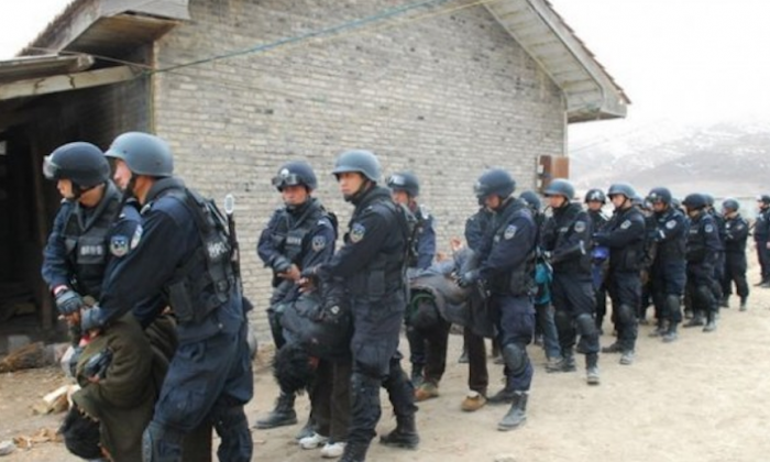 Tibetans are forced to bow down as they are taken away by Chinese security forces in 2011. Tibetan writers and artists are being targeted for arrest in China's latest crackdown. (From an Chinese online military forum)