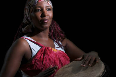 A file photo of an African woman playing the djembe. A top musician in Ghana urges his compatriots to embrace the traditional sounds, which he says Europeans and others around the world appreciate. (Shutterstock*)