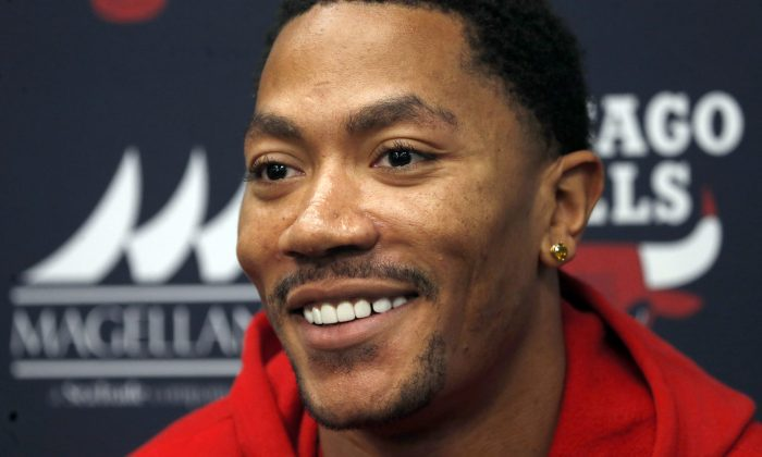 Chicago Bulls guard Derrick Rose smiles during an NBA basketball news conference about his injured knee Thursday, Dec. 5, 2013, at  the United Center in Chicago. (AP Photo/Charles Rex Arbogast)