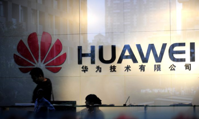 Staff and visitors walk pass the lobby at the Huawei office in Wuhan, central China's Hubei province on Oct. 8, 2012. (STR/AFP/GettyImages)