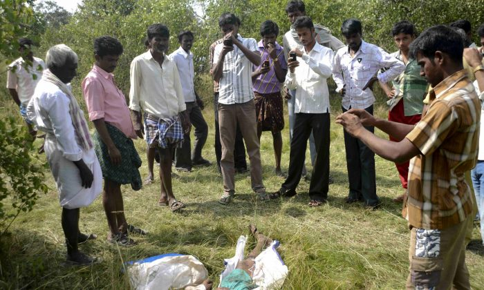 Indian onlookers use their mobiles to click photographs of the body of a farmer, Basappa, killed by a man-eating tiger on the edge of Bandipur Forest, about 80 kms from the city of Mysore in the southern state of Karnataka on December 4, 2013.  The Tiger was caught on Thursday. (STR/AFP/Getty Images)