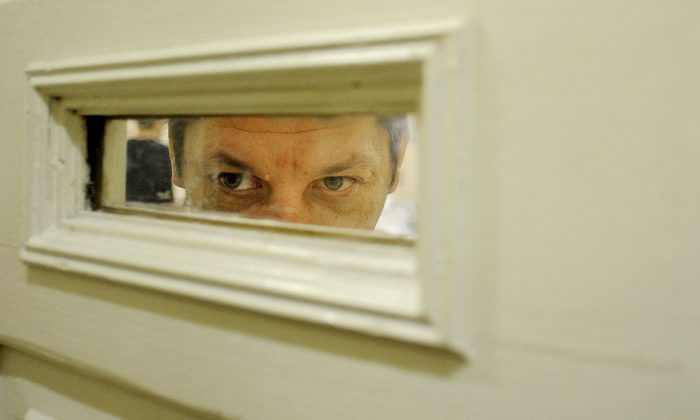 A patient looks through a window of the door in the Serbsky State Scientific Center for Social and Forensic Psychiatry, which has called for mandatory treatment of alcoholism and drug abuse. Moscow, Oct. 10, 2011. (Natalia Kolesnikova/AFP/Getty Images)