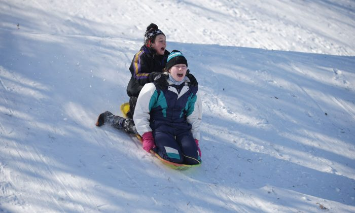 Children have fun sledding in a field. An increasing lack of free, unstructured time outdoors means kids are forgetting how to play, says an Ontario health and physical education consultant. (Chip Somodevilla/Getty Images)