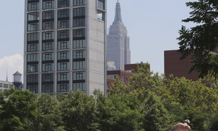 With the Empire State Building and a residential building in the background, a man sunbathes in Hudson River Park, Manhattan, New York, July 16, 2013. (Mary Altaffer/AP)