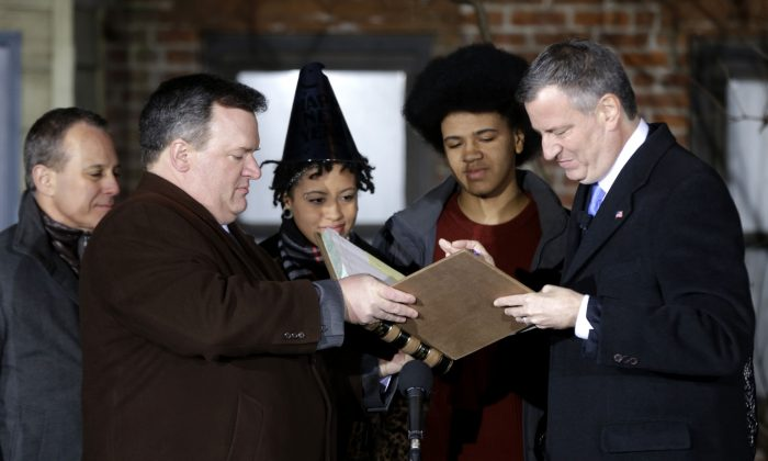 City Clerk Michael McSweeney (2nd L) assists Bill de Blasio (R), as he signs the oath of office while (L–R) State Attorney General Eric Schneiderman,  Chiara de Blasio, and Dante de Blasio look, New York, Jan. 1, 2014. De Blasio took the oath of office moments after midnight at his home in Park Slope, Brooklyn, his inauguration will be celebrated at noon on the steps of City Hall when he takes the oath again, which will be administered by President Bill Clinton. (AP Photo/Seth Wenig, Pool)