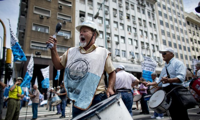 Port workers demonstrate outside the customs building in Buenos Aires, Argentina, Wednesday, Feb. 12, 2014. The protesters say the government is not paying retired port workers their state pension plan, affecting over 1,000 of their union members. (AP Photo/Victor R. Caivano)