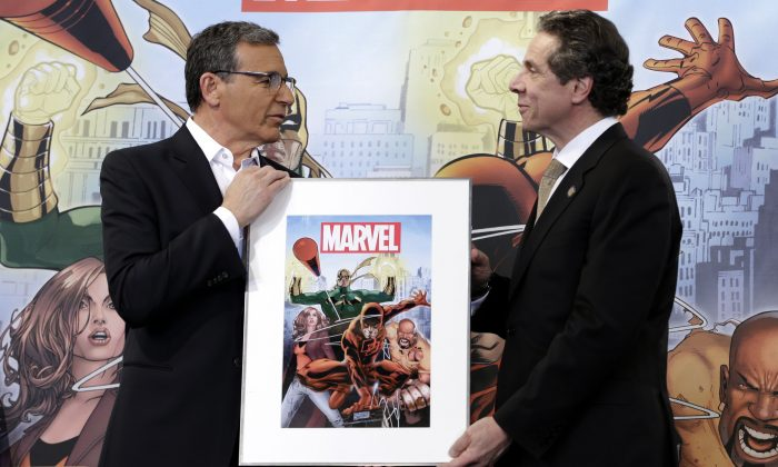 Disney CEO Bob Iger, left, presents New York Governor Andrew Cuomo with a signed poster during a news conference in New York, Wednesday, Feb. 26, 2014. Cuomo and Iger helped to announce the scheduled filming of a TV series based on Marvel characters in New York State. (AP Photo/Seth Wenig)