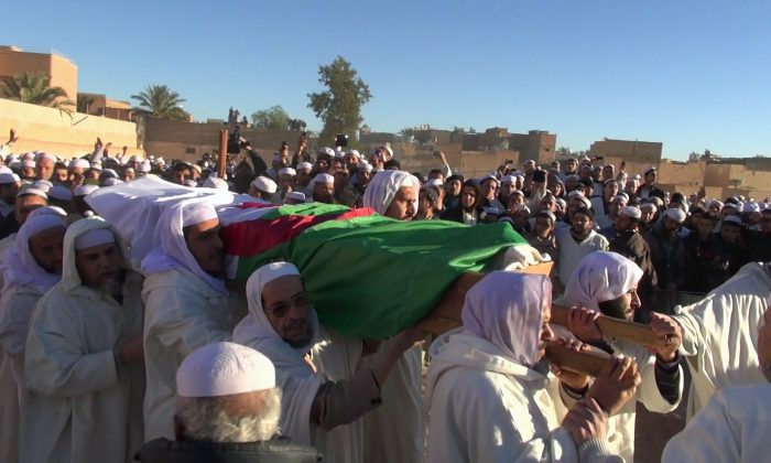 In this image taken Friday Feb. 7, 2014 Muslims carry the coffin of Azzedine Babaousmail, a Berber who died of his wounds on Thursday, in the desert city of Ghardaia, southern Algeria. Weeks of sectarian tension in a southern desert city is boiling over after the deaths of two Berber men in as many days, including one that a local politician said was killed in a street fight as police stood by. Ghardaia, on edge for months, is divided between Algeria's Mozabites, members of North Africa's original Berber inhabitants, and Sunni Muslim Arab migrants. (AP Photo/Anis Belghoul)