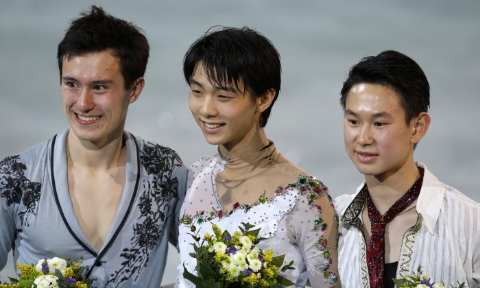 Yuzuru Hanyu of Japan, centre, Patrick Chan of Canada, left, and Denis Ten of Kazakhstan pose for photographs on the podium during the flower ceremony for the men's free skate figure skating final at the Iceberg Skating Palace during the 2014 Winter Olympics, Friday, Feb. 14, 2014, in Sochi, Russia. Hanyu placed first, Chan second and Ten third. (AP Photo/Darron Cummings)