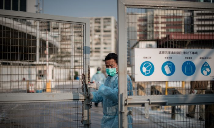 A security guard closes the gate of a live poultry market in Hong Kong on Jan. 28. There is a new outbreak of bird flu cases in China, where a new strain of the virus has re-emerged. (PHILIPPE LOPEZ/AFP/Getty Images)
