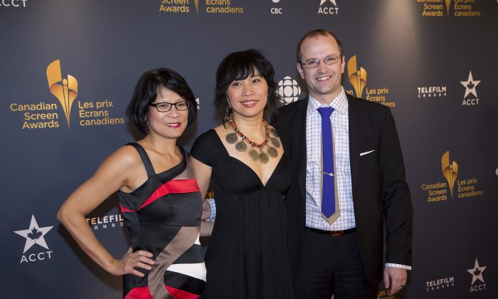 "MP Olivia Chow (L) poses with her stepson Mike Layton and actress Sook-Yin Lee. Lee was honoured with Best Actress in a Dramatic Program or Mini-Series for playing Chow in ""Jack,"" a biopic about late NDP leader Jack Layton, Chow's husband. In the press room, Lee spoke of the challenges and rewards of playing a real-life person who was there to guide her on set. She admitted this was intimidating, but noted that Chow was also very generous. ""She's an artist herself, and gave me a lot of room to interpret."" The actress said she set out to exteriorize Chow's inner world, but ended up putting so much into the role that she had to stop and question who she was.""It becomes very clear that personality is a construct."" Lee also noted it was both a challenge and a gift to portray the loss of a beloved person, an inevitable yet difficult part of life. ""It was very visceral to be able to walk through that and do it in a safe place—not just in crazy chaotic life, but in a fictional scenario. It was really good therapy,"" she said. (Evan Ning/Epoch Times)"