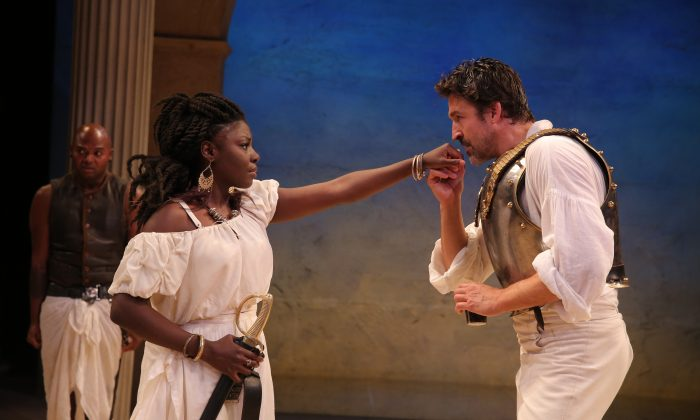 """(C–R) Cleopatra (Joaquina Kalukango) and her besotted Antony (Jonathan Cake), with Chivas Michael behind, as they appear in """"Antony and Cleopatra."""" (Joan Marcus)"""
