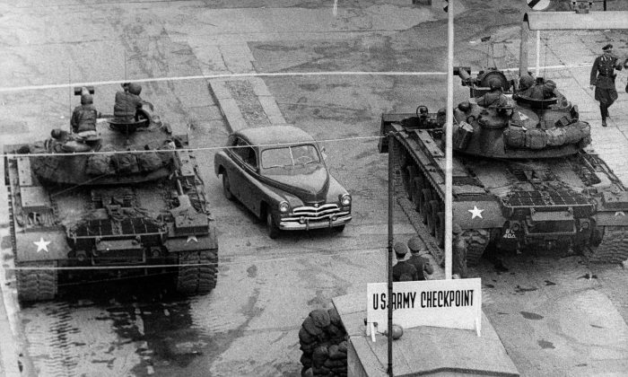 A car rides between US tanks, in October 1961, across the famous border of the American sector in Berlin, at Checkpoint Charlie crossing point, the only one in the Berlin Wall between East (Soviet sector) and West Berlin (American sector) used only by diplomats and foreigners. (AFP/Getty Images)