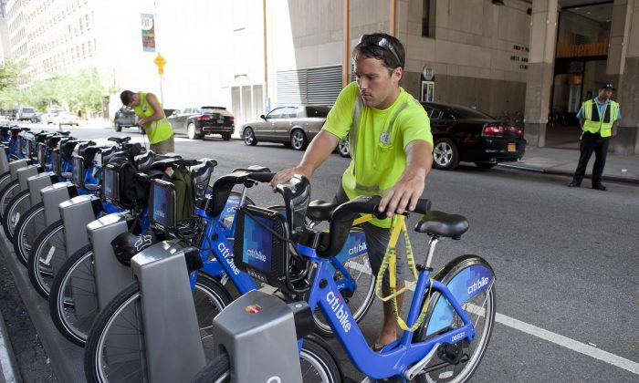 A maintenance  Citi Bikes crew member works on a bike share docking station at 7th Avenue and 27th Street, Manhattan, New York, July 5, 2013. (Samira Bouaou/Epoch Times)
