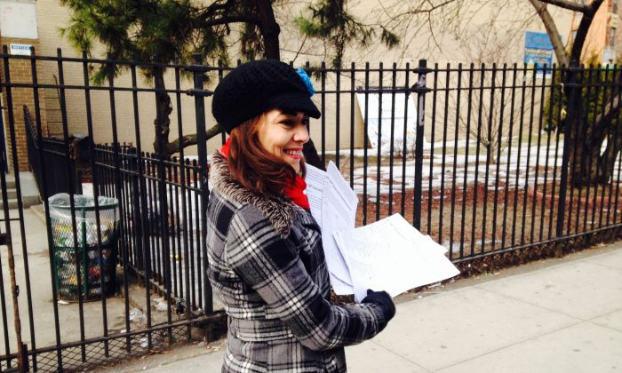 President of I.S. 52 Parent Association, Yuderka Valdez, holds petitions with signatures to stop the city from co-locating another school at I.S. 52, Inwood, Manhattan, New York, March 5, 2014. (Yi Yang)