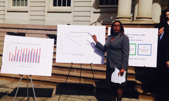 Public Advocate Letitia James points at chart indicating the increase in lunch participation after universal free lunch was adopted in selected public schools in New York, March 11, 2014. (Yi Yang)