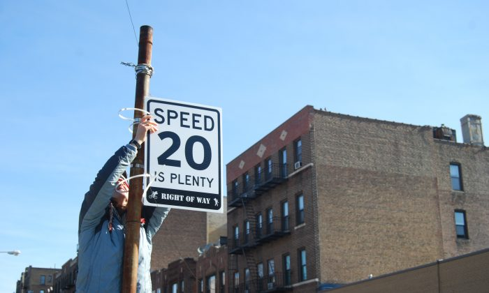 "An Astoria resident puts up a ""20 is Plenty"" speed limit sign in Queens, New York on March 16, 2014. (Catherine Yang/Epoch Times)"