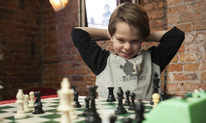 Lucas Foerster-Yialamas, 6, national first-grader category chess champion at the K12 Championship in Florida plays chess, at the Zinc Bar in Greenwich Village, New York, March 18, 2014. (Samira Bouaou/Epoch Times)