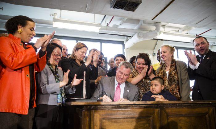 Mayor Bill de Blasio signs the paid sick leave bill at a converted factory in Brooklyn, New York, March 20, 2014. (Edward Dai/Epoch Times)