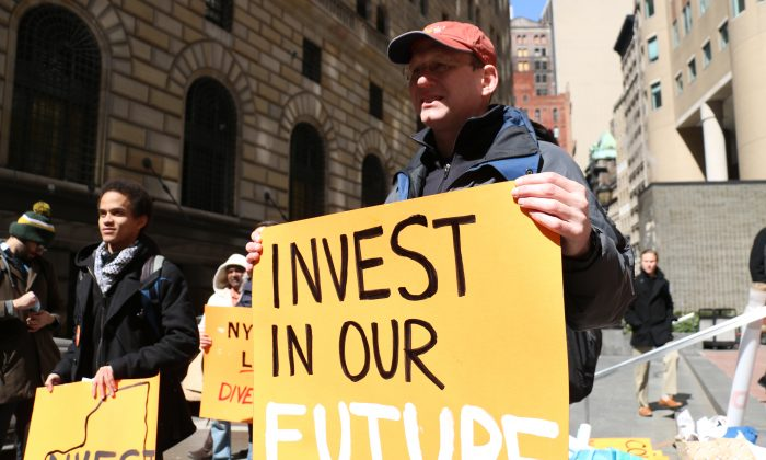 Participants in front of the state comptroller's Manhattan office call for pension fund's divestment of fossil fuel companies, in New York on March 27, 2014. (Allen Xie)