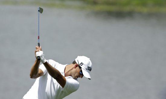 Adam Scott, of Australia, prepares to hit his second shot on the third hole