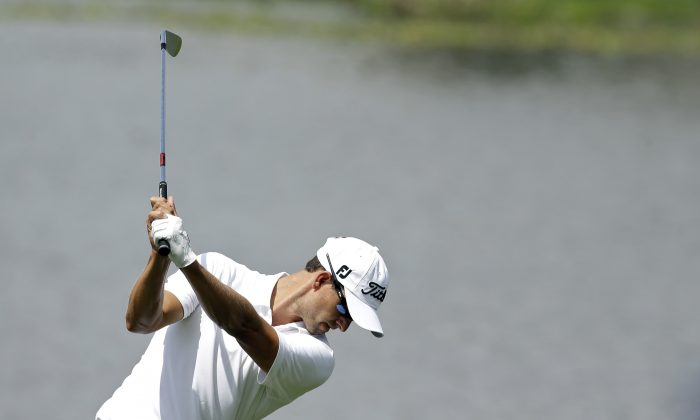 Adam Scott, of Australia, prepares to hit his second shot on the third hole during the third round of the Arnold Palmer Invitational golf tournament at Bay Hill Saturday, March 22, 2014, in Orlando, Fla. (AP Photo/Chris O'Meara)