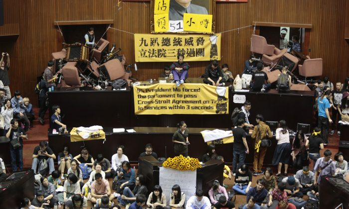 Students and protesters occupy the Taiwanese Parliament on March 19, in Taipei, Taiwan, to protest against the ruling Nationalist Party's attempt ratify a controversial service and trade agreement with China. Over 200 students broke into the Taiwan Parliament and took over the main chamber. (Ashley Pon/Getty Images)
