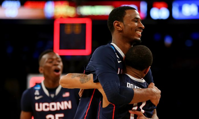 Amida Brimah #35, DeAndre Daniels #2 and Ryan Boatright #11 of the Connecticut Huskies celebrate after defeating the Iowa State Cyclones during the regional semifinal of the 2014 NCAA Men's Basketball Tournament at Madison Square Garden on March 28, 2014 in New York City. (Elsa/Getty Images)