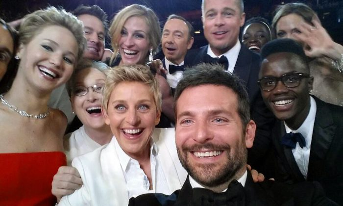 """This image released by Ellen DeGeneres shows actors front row from left, Jared Leto, Jennifer Lawrence, Meryl Streep, Ellen DeGeneres, Bradley Cooper, Peter Nyong'o Jr., and, second row, from left, Channing Tatum, Julia Roberts, Kevin Spacey, Brad Pitt, Lupita Nyong'o and Angelina Jolie as they pose for a """"selfie"""" portrait on a cell phone during the Oscars, March 2, 2014, in Los Angeles. (AP Photo/Ellen DeGeneres)"""