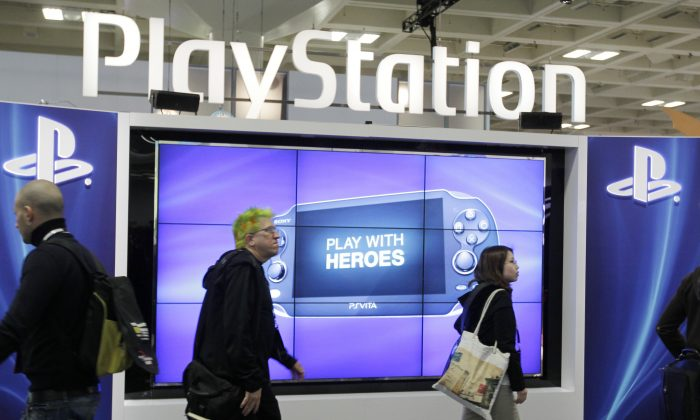 """Lizard Squad and Finest Squad have apparently been doing battle over PlayStation Network and Xbox Live.  This March 8, 2012 file photo shows attendees walking past the Sony PlayStation PS Vita console on display in the Sony PlayStation booth at the Game Developers Conference in San Francisco. Despite a refreshed focus on real-world issues at the 2014 GDC convention that kicks-off Monday, March 17, 2014, the ever-changing virtual world and how to view and interact with it will take center stage at GDC. PlayStation 4 creator Sony Corp. is expected to tease its rendition of virtual reality technology during a Tuesday presentation called """"Driving the Future of Innovation at Sony Computer Entertainment."""" (AP Photo/Paul Sakuma, file)"""