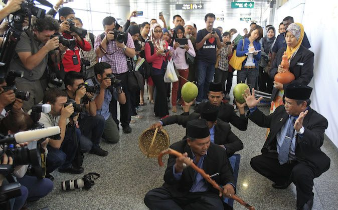 Malaysian well-known shaman Ibrahim Mat Zin, front right, uses spiritual methods and prayers to locate the missing Malaysia Airlines plane MH370 at Kuala Lumpur International Airport in Sepang, Malaysia, Wednesday, March 12, 2014. The missing Malaysian jetliner may have attempted to turn back before it vanished from radar, but there is no evidence it reached the Strait of Malacca, Malaysia's air force chief said Wednesday, denying reported remarks he said otherwise. The statement suggested continued confusion over where the Boeing 777 might have ended up, more than four days after it disappeared en route to Beijing from Kuala Lumpur with 239 people on board. (AP Photo/Lai Seng Sin)
