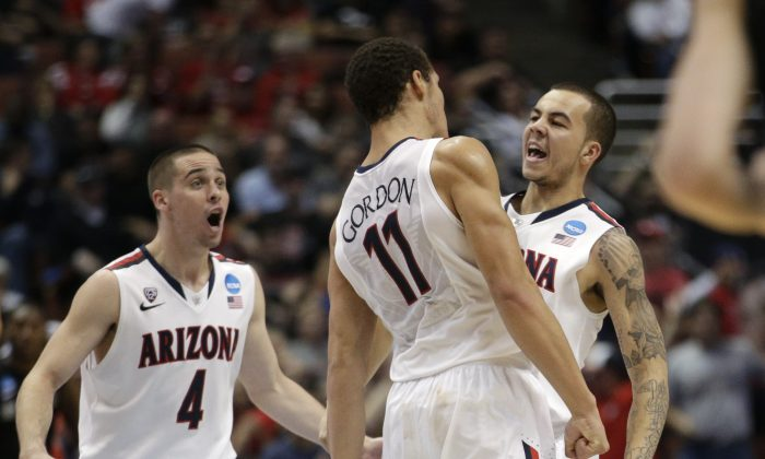 Arizona guard Gabe York, right, celebrates with T.J. McConnell (4) and Aaron Gordon (11) during the second half against San Diego State in a regional semifinal of the NCAA men's college basketball tournament, Thursday, March 27, 2014, in Anaheim, Calif. (AP Photo/Jae C. Hong)