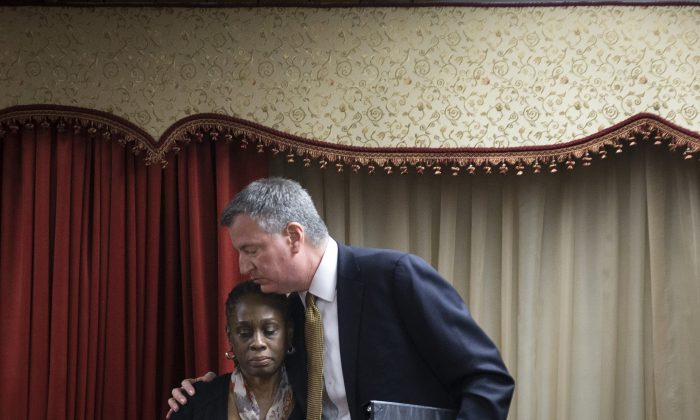 New York City Mayor Bill de Blasio (R) hugs his wife, Chirlane McCray, after speaking at the Church of God of Third Avenue as the congregation welcomed members of the Spanish Christian Church after the church was destroyed by Wednesday's explosion in the East Harlem neighborhood of New York, March 16, 2014. (AP Photo/John Minchillo)