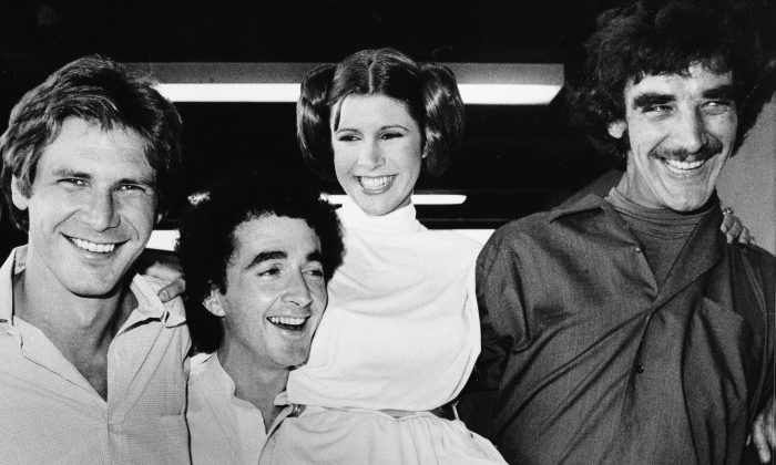 From left, Harrison Ford who played Han Solo, Anthony Daniels who played the robot C3P0, Carrie Fisher who played the princess, and Peter Mayhew who played the Wookie, Chewbacca, are shown during a break from the filming of a television special presentation in Los Angeles, Ca., Oct. 5, 1978.  (AP Photo)