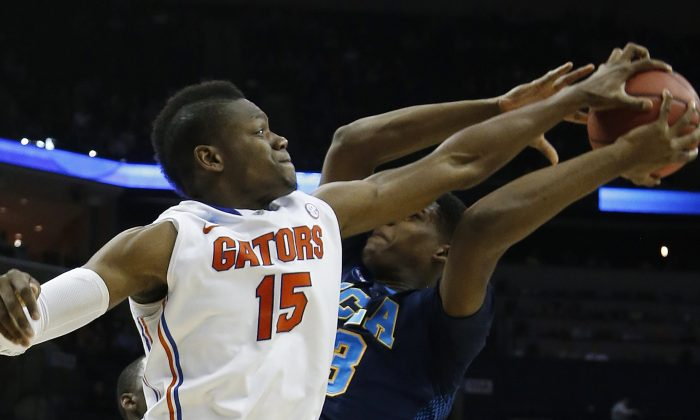 Florida forward Will Yeguete (15) blocks a shot by UCLA forward/center Tony Parker (23) during the second half in a regional semifinal game at the NCAA college basketball tournament, Thursday, March 27, 2014, in Memphis, Tenn. (AP Photo/Mark Humphrey)