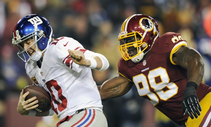 In this Dec. 1, 2013 file photo, New York Giants quarterback Eli Manning, left, is sacked by Washington Redskins outside linebacker Brian Orakpo (98) during the first half of an NFL football game in Landover, Md. (AP Photo/Nick Wass, File)