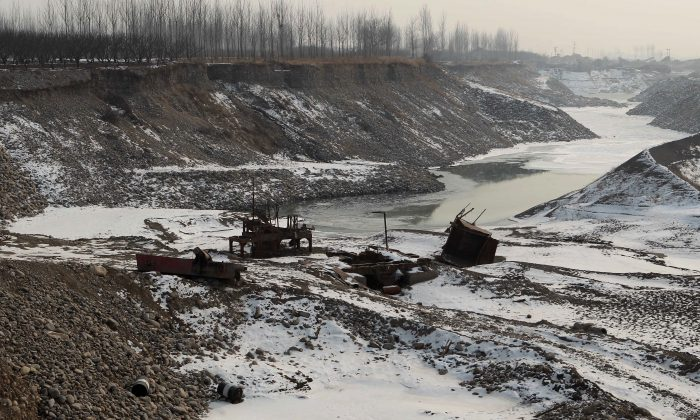 Discarded machinery parts are seen in the Juma river after gravel mining operations, Jan. 8, 2013. Many waterways in China have become heavily contaminated with toxic waste. (STR/AFP/Getty Images)