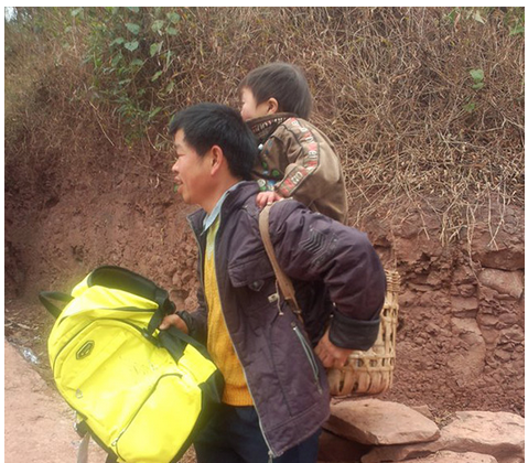 Yu Xukang wears a special bamboo basket for his 12-year-old son Xiao Qiang to stand in, while he carries him to and from school. (Screenshot/People's Daily)