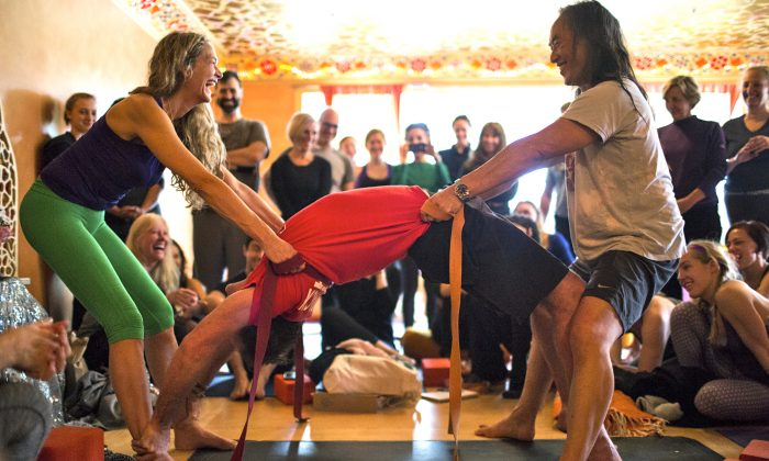 Colleen Saidman Yee, left, and Rodney Yee joyously help a student release into a posture at their Sag Harbor location.   The couple opens their NYC studio in March. (courtesy of Yoga Shanti)