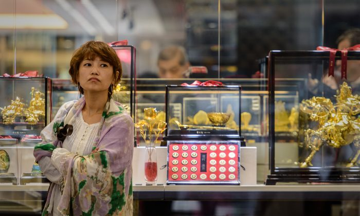 A woman looks on in front of a jewellery shop in Hong Kong on April 16, 2013. (PHILIPPE LOPEZ/AFP/Getty Images)