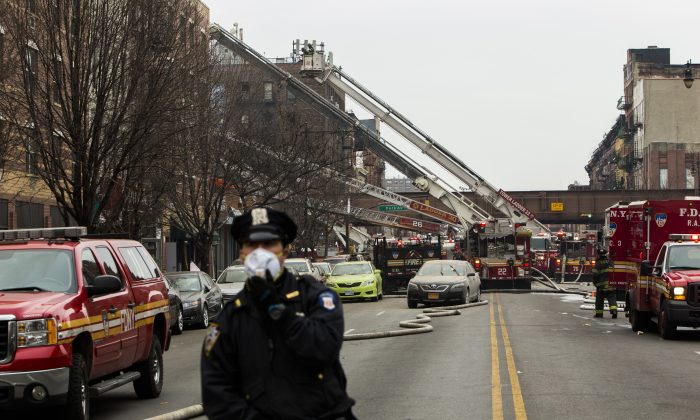 A police officer near the scene of a gas leak explosion that caused two buildings to collapse on Park Avenue and 116th street in the Harlem neighborhood of Manhattan March 12, 2014 in New York City. Reports of an explosion were heard before the collapse of two multiple-dwelling buildings that left at least 17 injured. (Christopher Gregory/Getty Images)
