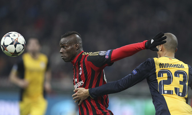 AC Milan forward Mario Balotelli, left, vies for the ball with Atletico Madrid defender Miranda, of Brazil, during a Champions League, round of 16, first leg, soccer match between AC Milan and Atletico Madrid at the San Siro stadium in Milan, Italy, Wed., Feb. 19, 2014. (AP Photo/Antonio Calanni)