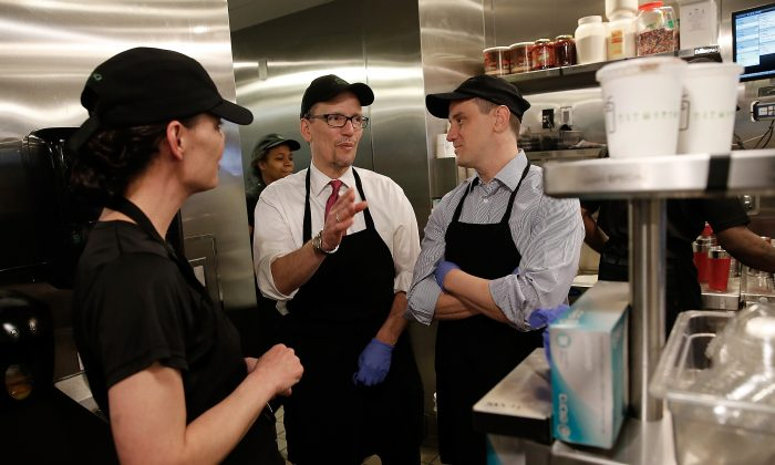 U.S. Labor Secretary Thomas Perez (C) talks with Shake Shack employee Lani Thompson (L) while touring the restaurant with Shake Shack CEO Randy Garutti (R) in Washington, D.C., on March 21, 2014. (Win McNamee/Getty Images)